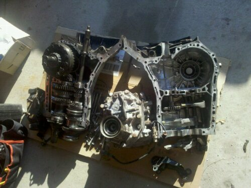 photo of a Subaru Impreza WRX 5 speed transmission opened up, you can see 2nd gear missing some teeth, also visible are shift selector forks, synchro gears, an upgraded front LSD limited slip differential, and the center differential section removed