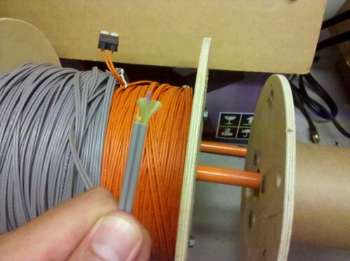 Fiber optic cable for computer network, gray with stripped insulation end exposing fiber